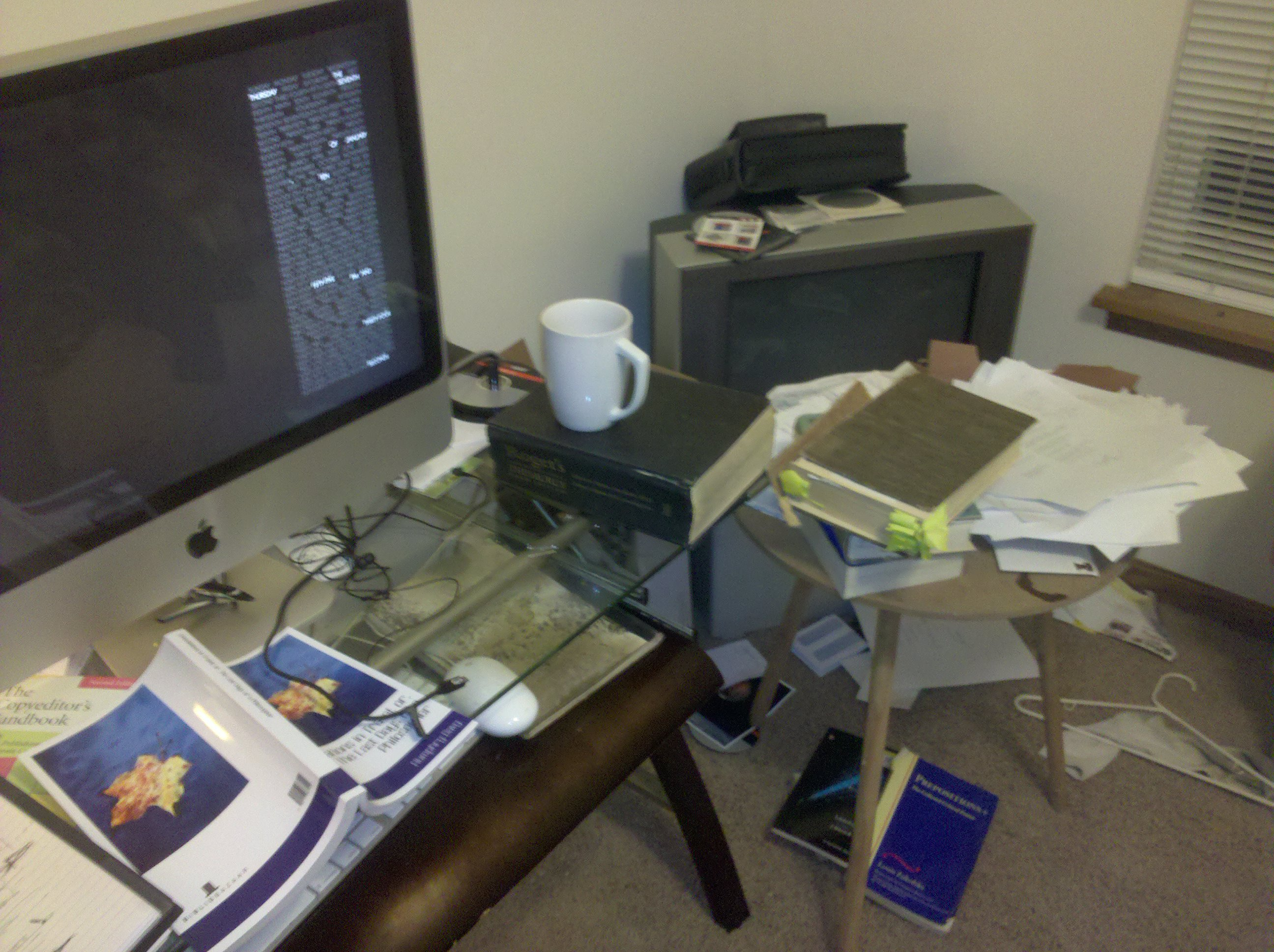 A desk and table buried uner a flurry of paperwork, both personal and professional